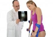 Junge Frau an Krücken bei Arzt