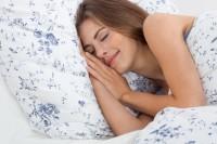 Junge brünette hübsche Frau schäft auf einem Kissen