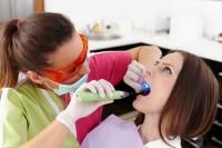 Zahnärztin versiegelt Zahn mit Kunststoff und härtet dieses mit Licht